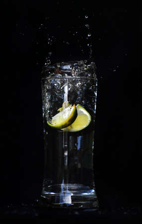 dropping lime slices into a cup of lime juice