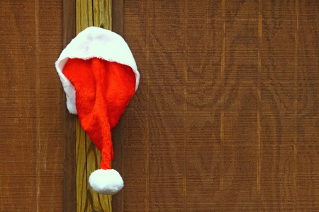 Iimage of Santas hat hanging on a wooden backdrop with copy space. Stock Photo