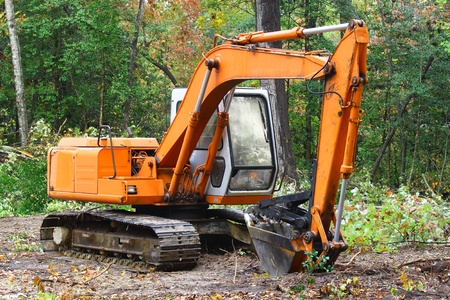 else: A construction Excavator used forexcavating of trees debris and anything else needed resting on the ground outside in the woods with room for your text.