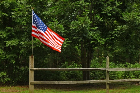 green flag: An American flag on a fence post blowing in the wind on a summer day with room for your text