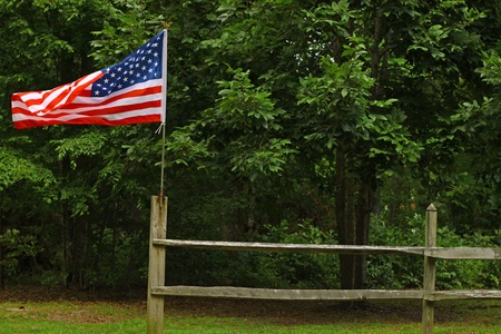 An American flag flying high and proud on a fence along the woods with room for your text. Stock Photo - 12156336