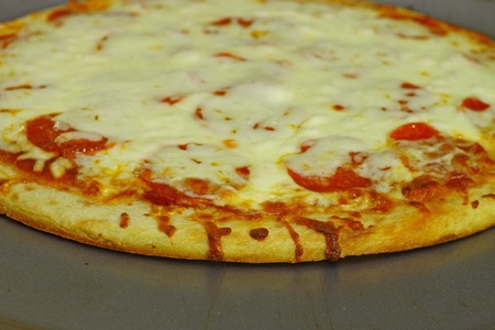 A fresh baked extra Pepperoni and extra Cheese Pizza Pie on the pie pan using a shallow depth of field and selective focus Imagens