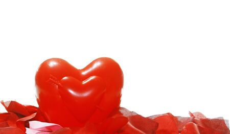 A red heart among red and pink petals isolated on white with room for your text.