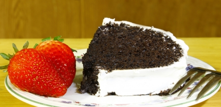 A slice of a white vanilla iced chocolate fudge cake with two fresh strawberries on the side of the ceramic platewith a fork using a shallow depth of field and selective focus on the front strawberry  Stock Photo