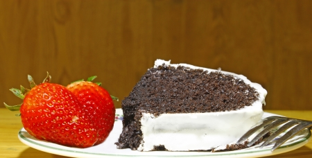 A slice of a white vanilla iced chocolate fudge cake with two fresh strawberries on the side of the ceramic platewith a fork using a shallow depth of field and selective focus on the front strawberry  photo