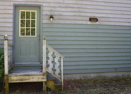 stoop: A small set of steps leading up to a small stoop and a doorway