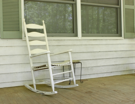 An old white painted wooden rocking chair sitting outside on a dirty front porch photo