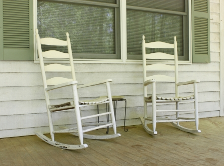 Two old white painted wooden rocking chairs on a front porch