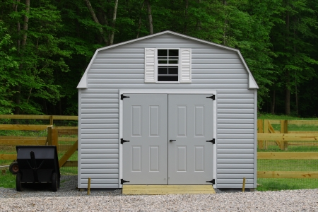 A nice new storage shed outside of a fenced in  back yard with a trailer beside it with room for your text. Stock Photo