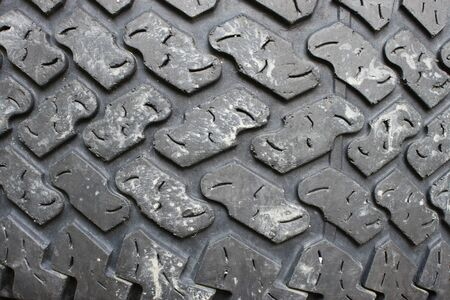 An old dirty tire tread pattern to be used as an abstract background with room for your text.