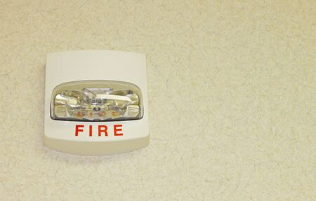 A Fire alarm on a textured wall with room for your text. photo