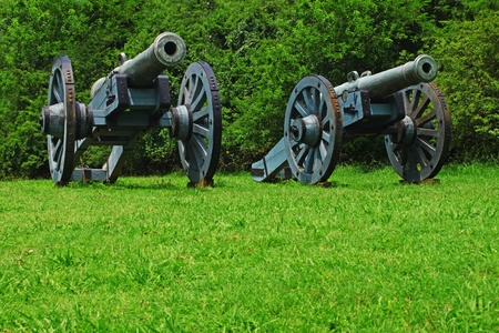 Two vintage antique Civil War Canons in a field overlooking Yorktown Virginia and the york river prepared to protect the county at all cost 免版税图像