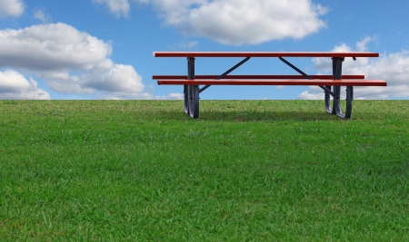 A Picnic table on a summer day with a bright blue cloud filled sky in the background and room for your text. Stock Photo