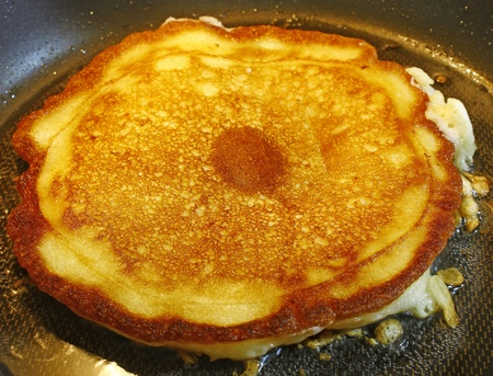 A fresh golden brown cooking breakfast pancake being cooked in grease creating a crispy edge in a hot pan Stock Photo