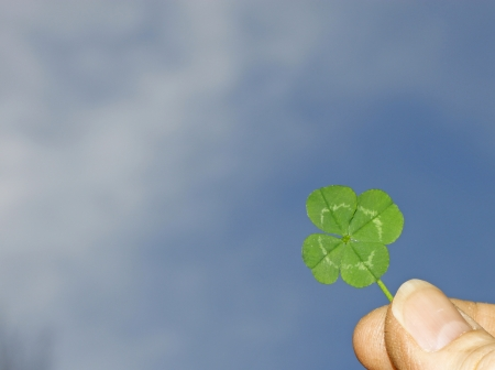 A mans thumb and finger grasbing a four leaf clover and holding it to the beautiful blue sky with room for your text. Stock Photo - 15150849
