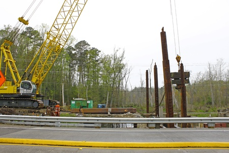 drydock: GLOUCESTER, VA, USA - MARCH 31:A  crane lowering supports for the drydock in the bridge replacement project over the ware river on Main Street. on March 31, 2012 in Gloucester, VA, USA Editorial