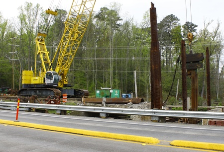 GLOUCESTER, VA, USA - MARCH 31:A large crane lowering steel posts at the bridge replacement project over the ware river on Main Street. on March 31, 2012 in Gloucester, VA, USA