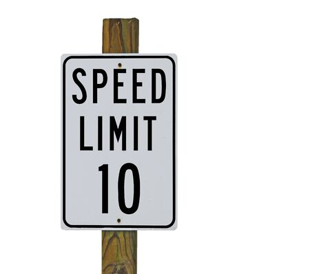 miles: A ten miles per hour speed limit sign at the entrance to a parking lot.