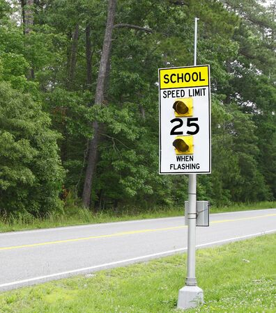 A School Speed limit sign with flashing lights along the edge of the road. photo