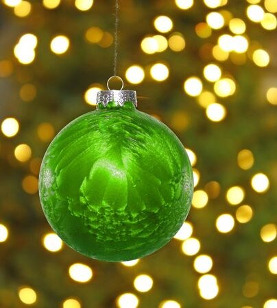 A big green hanging Christmas ball decoration in front of a blown out christmas tree background and lights