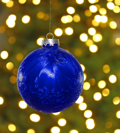 A big blue hanging Christmas ball decoration in front of a blown out christmas tree background and lights