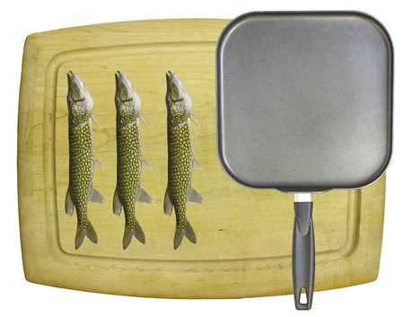 An old wooden cutting board isolated on white with a square non-stick frying pan and three chain pickerel