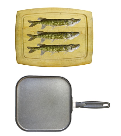 An old wooden cutting board isolated on white with a square non-stick frying pan and three chain pickerel photo