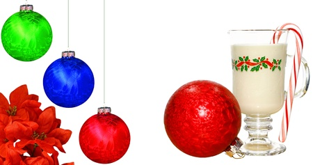 A cold glass of eggnog on white with a peppermint candy cane in it, a poinsettia flower and Christmas Balls with room for your text. Stock Photo