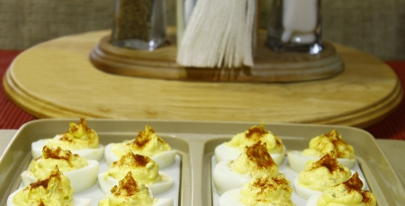 Deviled eggs in a plastic container on the table with napkins,salt and pepper to be ate for part of Thanksgiving dinner