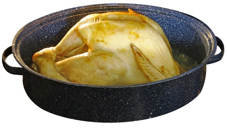 A large Golden Brown Turkey for Thanksgiving dinner cooking in a ceramic pan isolated on white Stock Photo