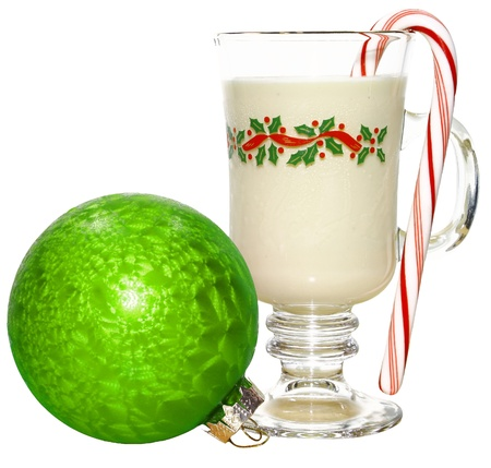 A cold glass of eggnog isolated on white with a peppermint candy cane in it and a Christmas Ball along side of it with room for your text.