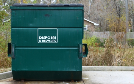 dumpster: A large green disposal and recycling dumpster parked outside on a concrete slab