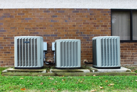 A group of three industrial sized air conditioners along a brick wall