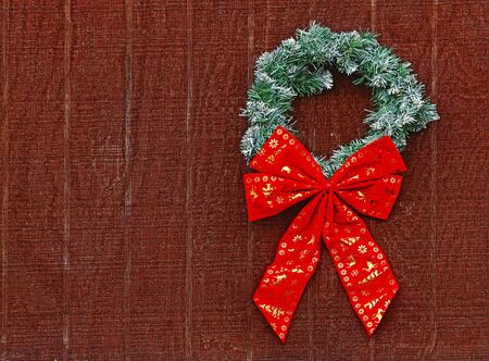 A green and white fake snow covered Christmas wreath with one large red and golden bow on a brown wooden background with room for your text