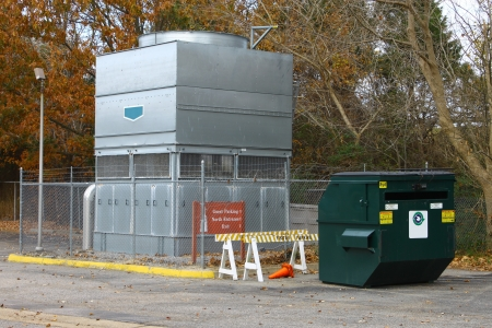 fuel provider: A large barbed wire fenced in industrial heat pump AC system and a recycle dumpster for a large facility