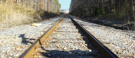 An old rarely used railroad track used for transporting oil and gas to and from the oil refinery and storage tanks photo
