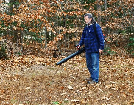A middle aged long gray haired white male outside working on a fall day blowing leaves out in the yard Stock Photo - 16884219