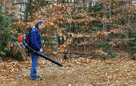 A middle aged long gray haired white male outside working on a fall day blowing leaves out in the yard photo