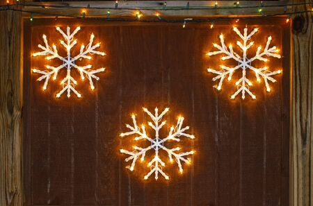 backdrop: Outdoor Christmas snowflake decorations against a brown wooden backdrop with room for your text.