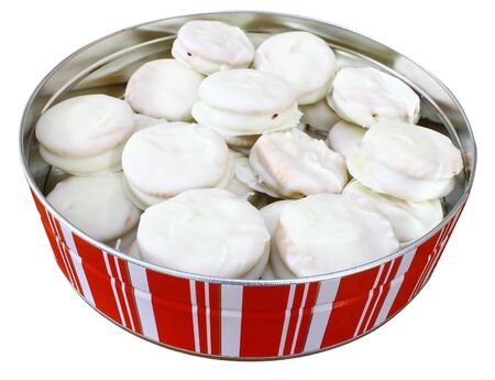 A round Christmas holiday tin full of white chocolate covered peanut butter crackersisolated on white