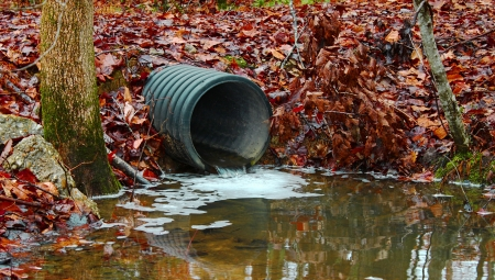 flowing water: A waste water drainage pipe redirecting water and polluting the environment as well