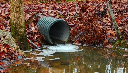 contaminacion ambiental: Un tubo de drenaje de aguas residuales redirigir el agua y la contaminaci�n del medio ambiente, as� Foto de archivo