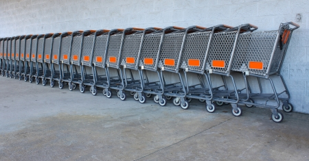 Store shopping carts lined in a row together against a wall outside of a store
