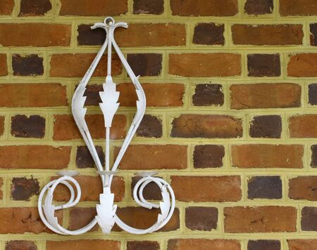 morter: An old metal, antique, vintage candle holder mounted on a brick wall of a buliding Stock Photo