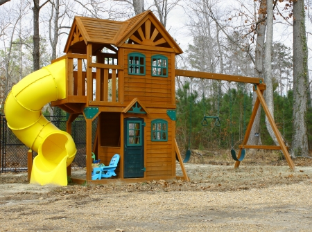 wood lawn: A childs playset swing and slide outside on a cloudy winter day