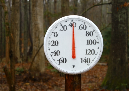 A new outdoor spring thermometer on a pole reading the outdoor winter temperature using a shallow depth of field and selective focus with room for your text.