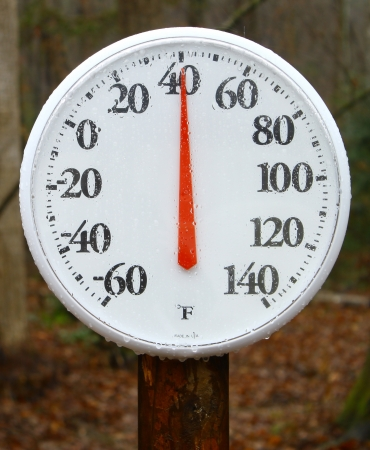 A new outdoor spring thermometer on a pole reading the outdoor winter temperature using a shallow depth of field and selective focus with room for your text.  photo