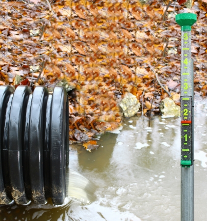 A waste water drainage pipe re-routing the water flow and polluting the environment at the same time with a rain gauge to show how much rain there was Stock Photo