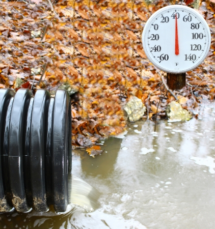 A waste water drainage pipe re-routing the water flow and polluting the environment at the same time with an outdoor thermometer showing the current temperature Stock Photo - 17755510