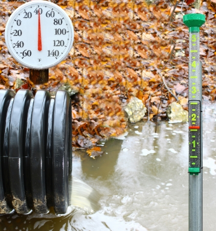 depth measurement: A waste water drainage pipe re-routing the water flow and polluting the environment at the same time with a rain gauge to show how much rain there was Stock Photo
